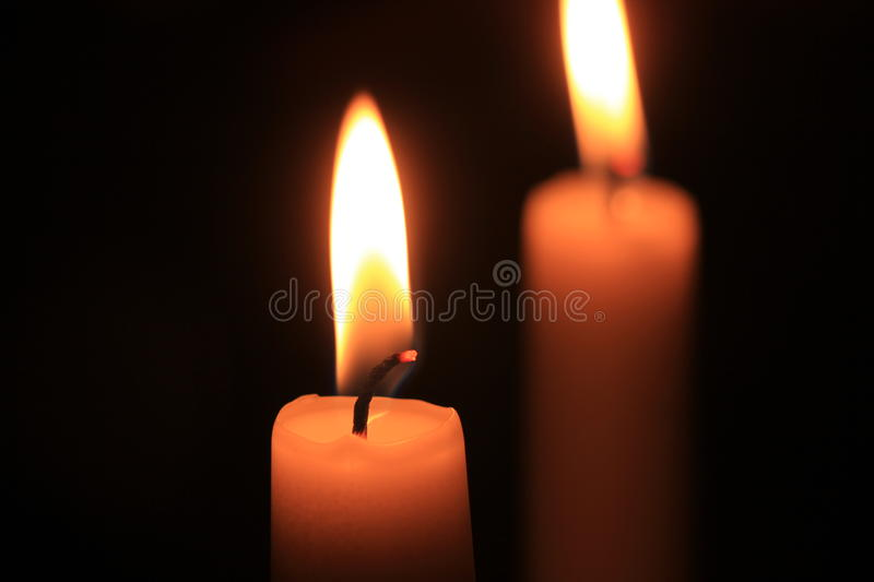 Burning candle in the dark stock images