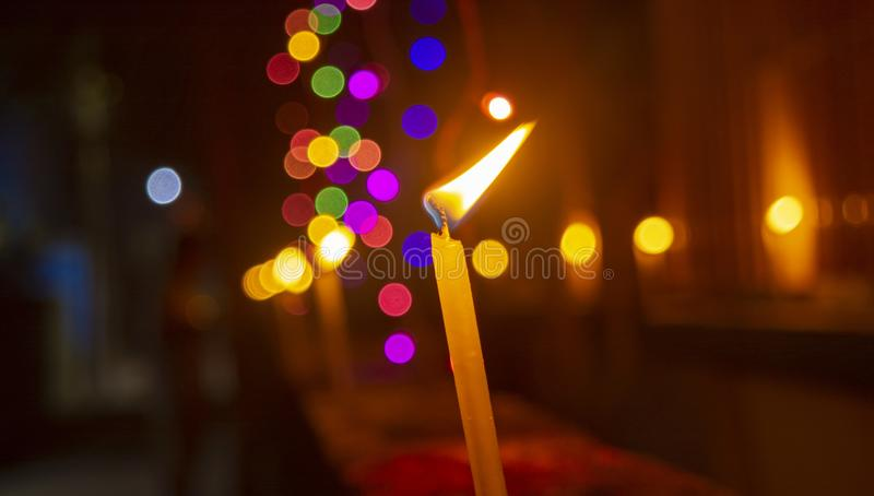 Burning Candle With Faint Colored Lights In Background. royalty free stock photography