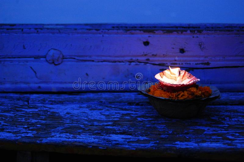 Burning candle and flowers. Close-up. Hinduism. stock photos
