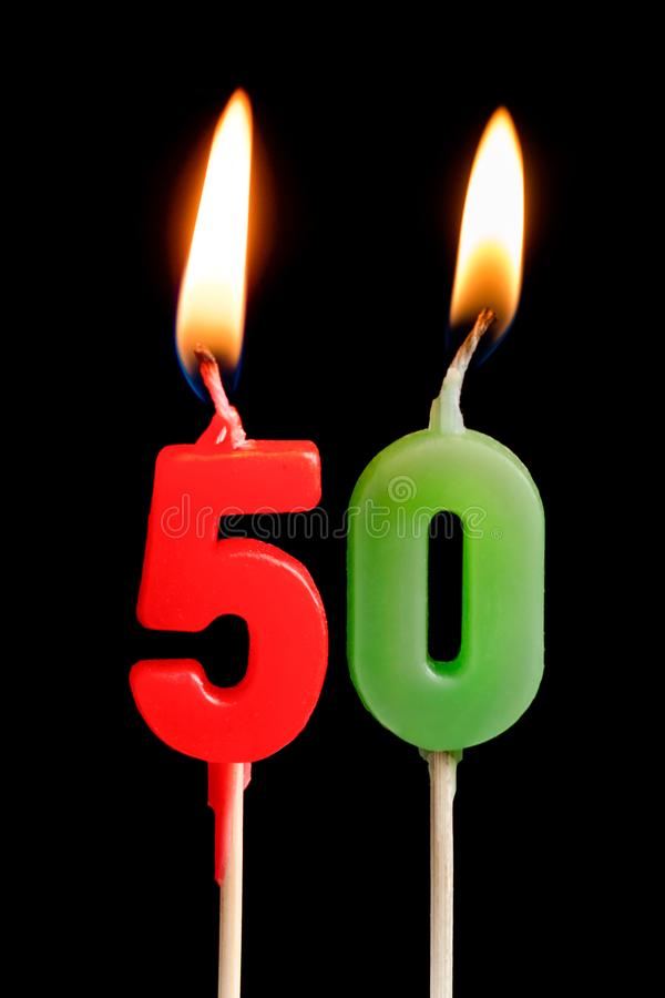 Burning candle in the form of five figures numbers, dates for cake on black background. The concept of celebrating a bi stock photos