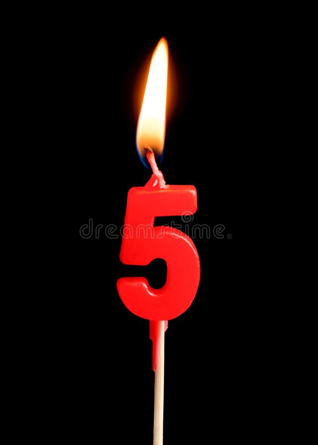 Burning candle in the form of five figures numbers, dates for cake isolated on black background. royalty free stock images