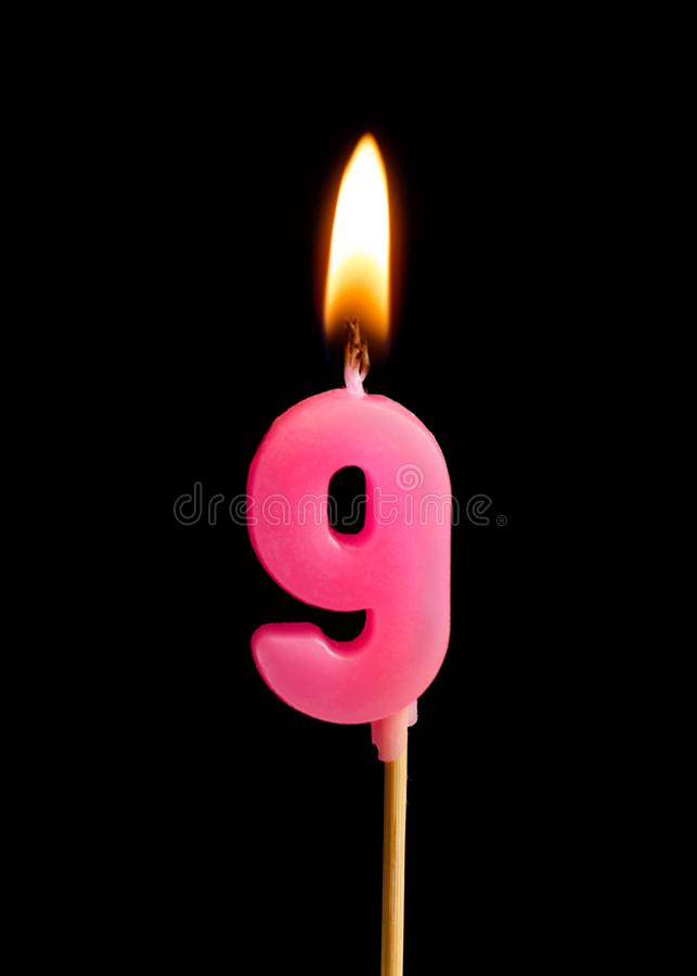 Burning candle in the form of nine figures numbers, dates for cake isolated on black background. stock images