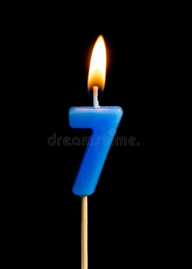 Burning candle in the form of seven figures numbers, dates for cake isolated on black background. stock photography