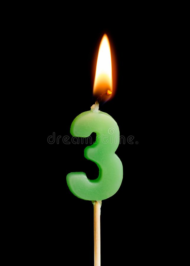Burning candle in the form of three figures numbers, dates for cake isolated on black background. stock image