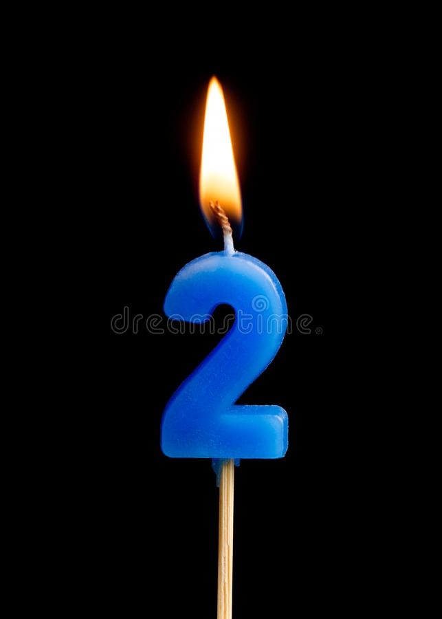 Burning candle in the form of two figures numbers, dates for cake isolated on black background. stock photo