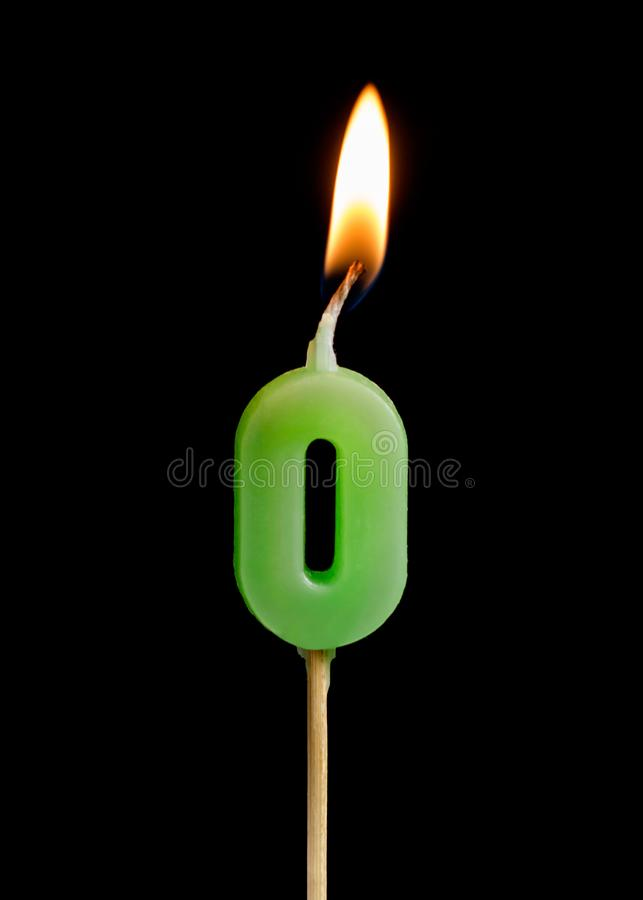 Burning candle in the form of zero figures numbers, dates for cake isolated on black background. stock photography