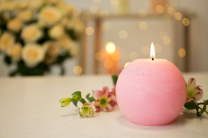 Burning candle and fresh flowers on table against blurred background stock photos
