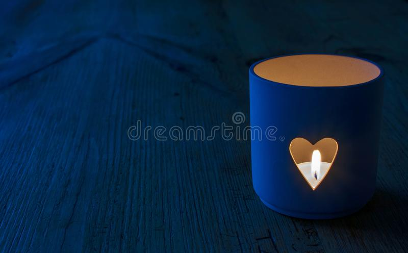 Heart shaped candle holder in blue tones. A burning candle inside a heart shaped candle holder, blue tones. Concept could be used for depression, bereavement stock images
