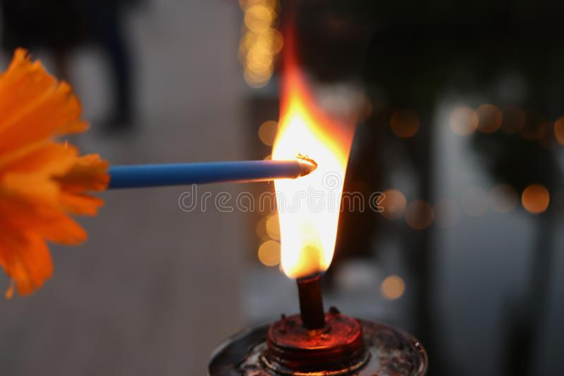 A burning candle from  the lantern in dark tone royalty free stock photo