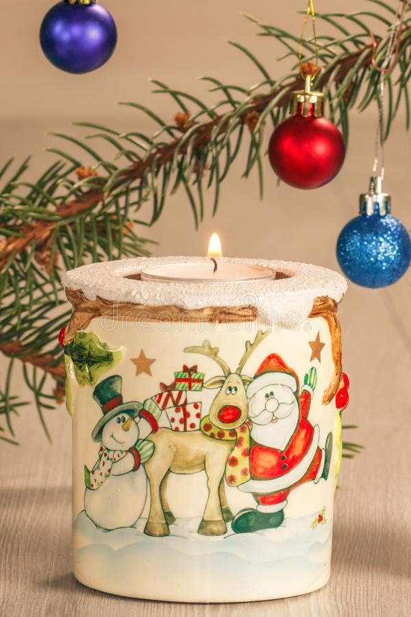 Burning candle and natural fir tree branches with Christmas ornament on grey wooden boards stock images