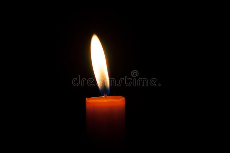 A burning candle at night. Symbol of life, love and light, protection and warmth. Candle flame glowing on a dark background. A burning candle at night. Candle royalty free stock photos