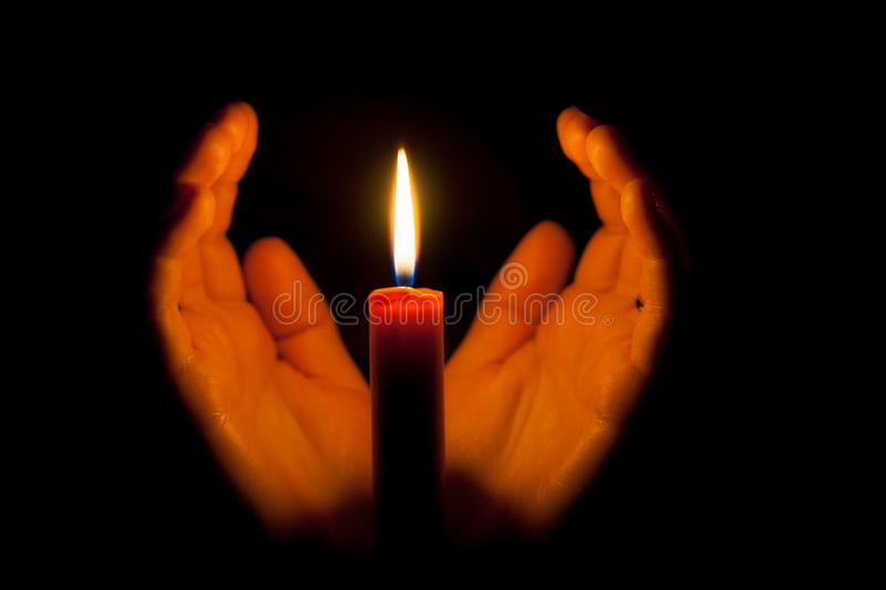 A burning candle at night, surrounded by the hands of a woman. Symbol of life, love and light, protection and warmth. stock photos