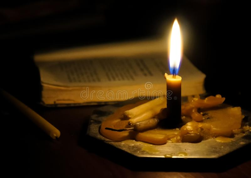 Burning candle and prayer book stock image