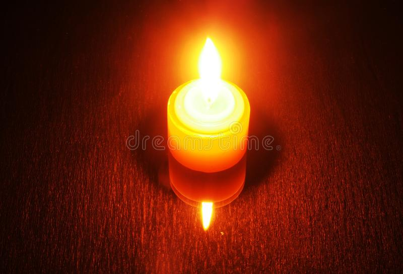 Burning candle on a reflective table. Visible candle and its ref. Lection. On a black background. Still life royalty free stock image