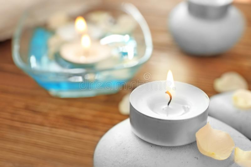 Burning candle with spa stone on table, closeup stock photos