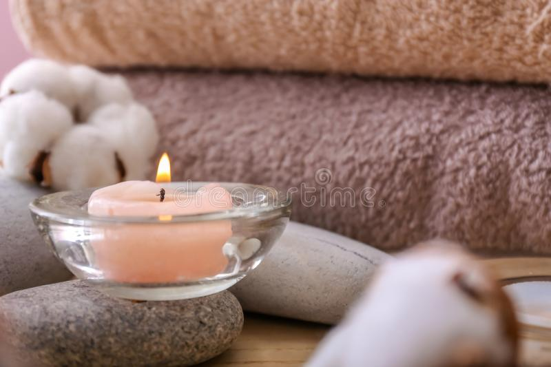 Burning candle, spa stones and cotton flowers on table, closeup stock image