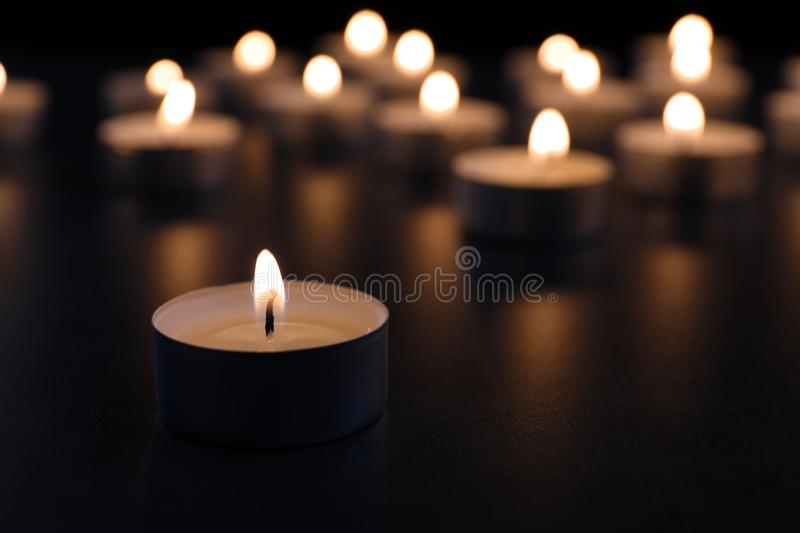 Burning candle on table in darkness, closeup. With space for text. Funeral symbol royalty free stock images