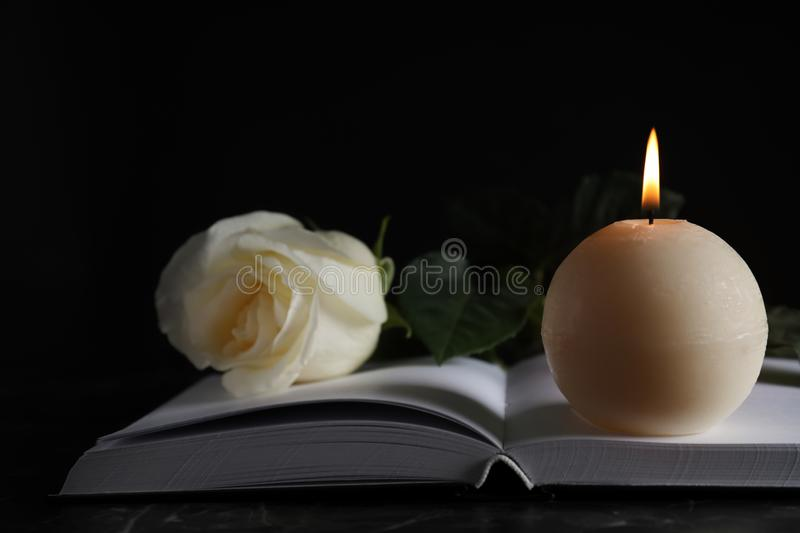 Burning candle, white  and book on table in darkness, closeup. Funeral symbol. Burning candle, white rose and book on table in darkness, closeup. Funeral symbol royalty free stock images