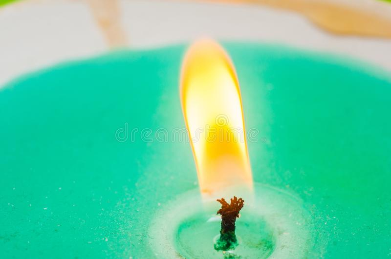 Burning candle wick with blue wax closeup on black background. Macro shooting.  royalty free stock photography
