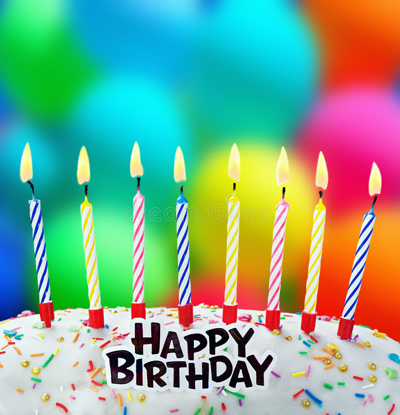 Burning candles on a birthday cake. On the background of balloons royalty free stock photo