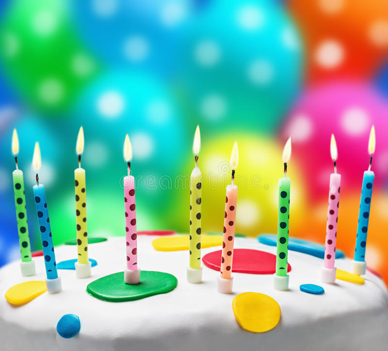 Burning candles on a birthday cake. On the background of balloons stock photos