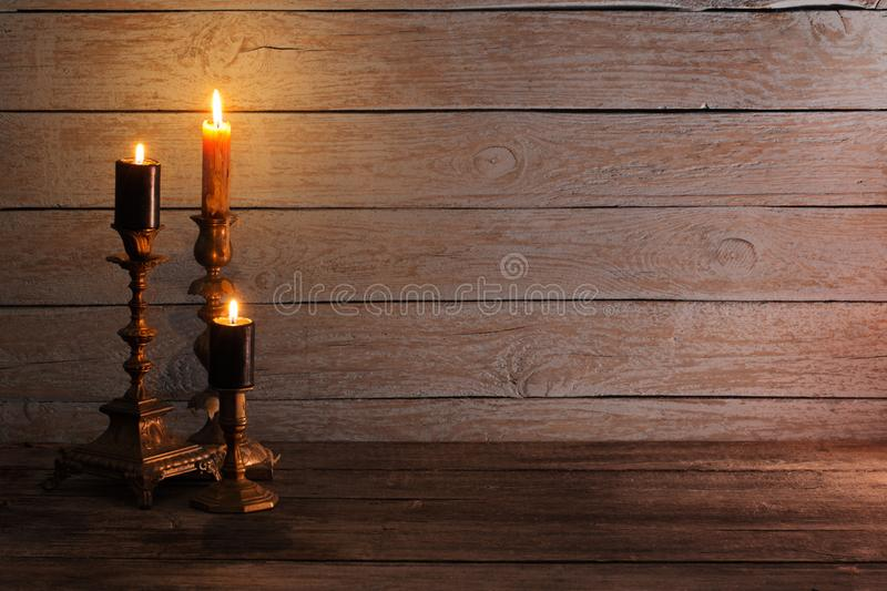 Burning candles in candlesticks on old wooden background royalty free stock photography