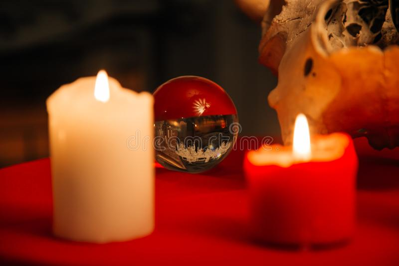 Burning candles and crystal ball. Wicca, esoteric, divination and occult background with vintage magic objects. For mystic rituals royalty free stock photo