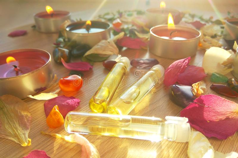 Burning candles with essential spa oil, rose flower petals and colorful gems on wooden background royalty free stock photography