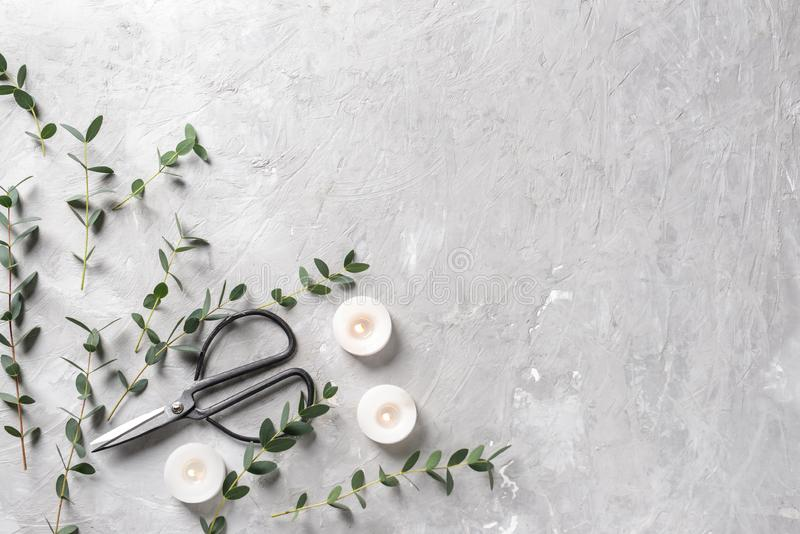 Burning candles with eucalyptus branches and scissors on grey background stock photography