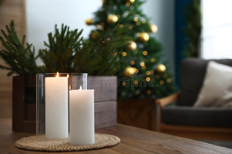 Burning candles and fir branches on table in room decorated for Christmas. Burning candles and fir branches on wooden table in room decorated for Christmas royalty free stock image