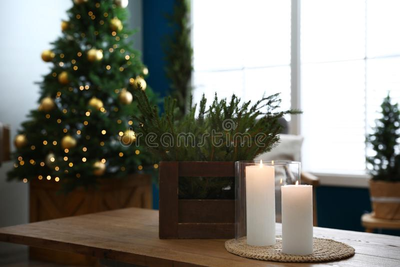 Burning candles and fir branches on table in room decorated for Christmas. Burning candles and fir branches on wooden table in room decorated for Christmas stock photography