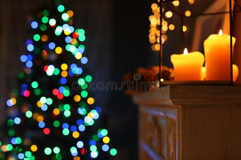 Burning candles on fireplace and Christmas tree royalty free stock photos
