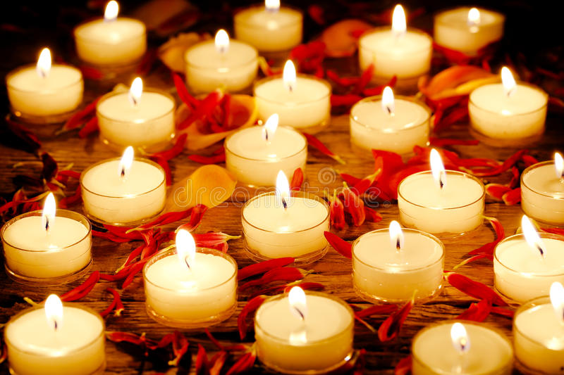 Burning candles. With flower petals on wooden surface royalty free stock image