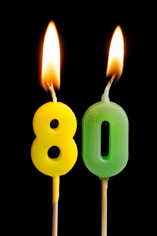 Burning candles in the form of eighty figures numbers, dates for cake on black background. The concept of celebrating a. Birthday, anniversary, important date stock image