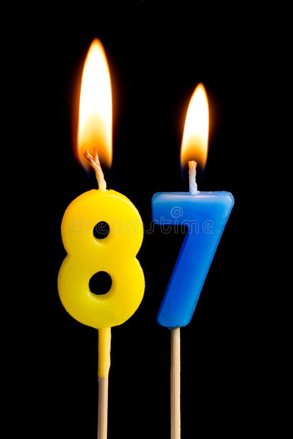 Burning candles in the form of 87 eighty seven numbers, dates for cake isolated on black background. The concept of celebrating. A birthday, anniversary royalty free stock photos