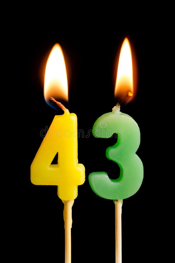 Burning candles in the form of 43 forty three numbers, dates for cake isolated on black background. The concept of celebrating a stock photo