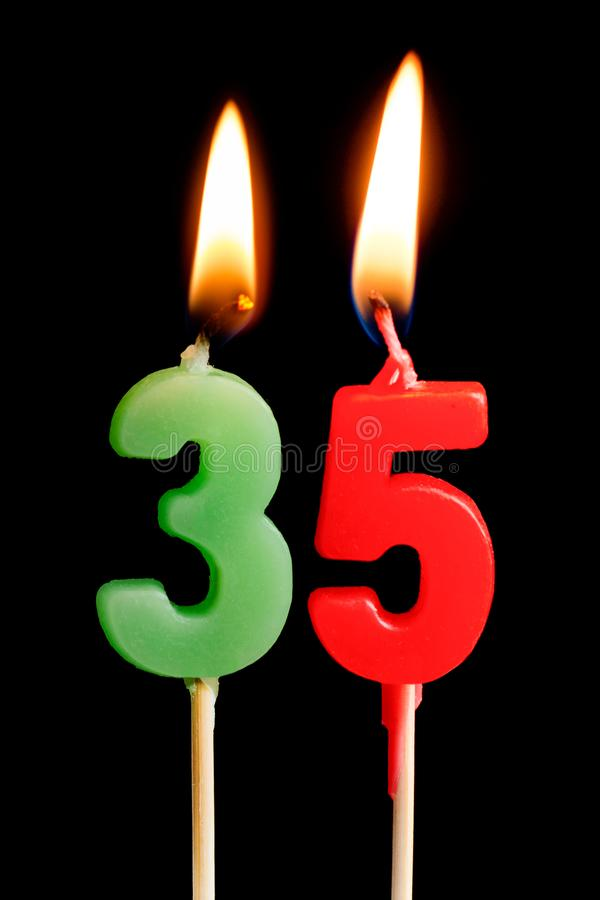 Burning candles in the form of 35 thirty five figures numbers, dates for cake isolated on black background. The concept of celeb royalty free stock photo