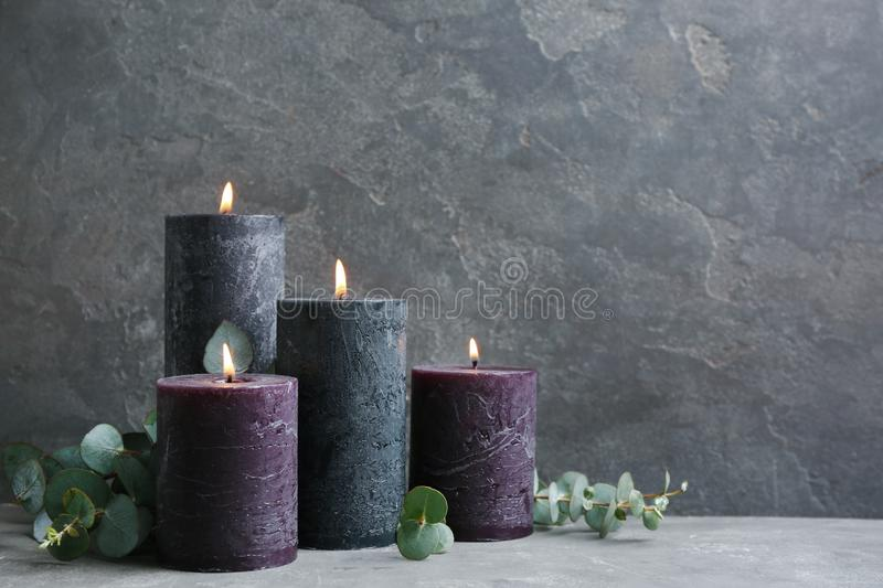 Burning candles and green branches on grey , space for text. Burning candles and green branches on grey table, space for text stock images