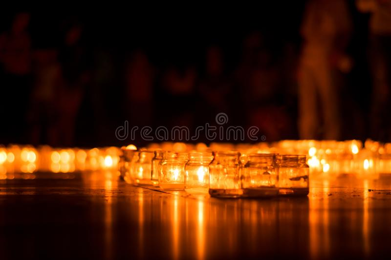 Burning candles in jars on a holiday with people and children memorial wedding day event. Burning candles bokeh in jars on a holiday with people and children royalty free stock photography