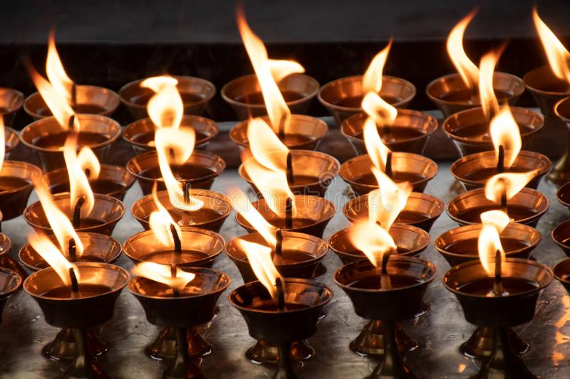 Burning candles light background.Candle flame at night Texture of Candle in Buddhism stock photography