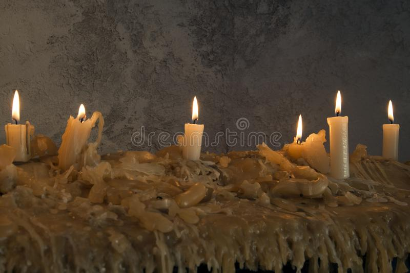 Burning candles on melted wax.many burning candles.Many burning candles. The flames caused by burning are beautiful lines royalty free stock photography