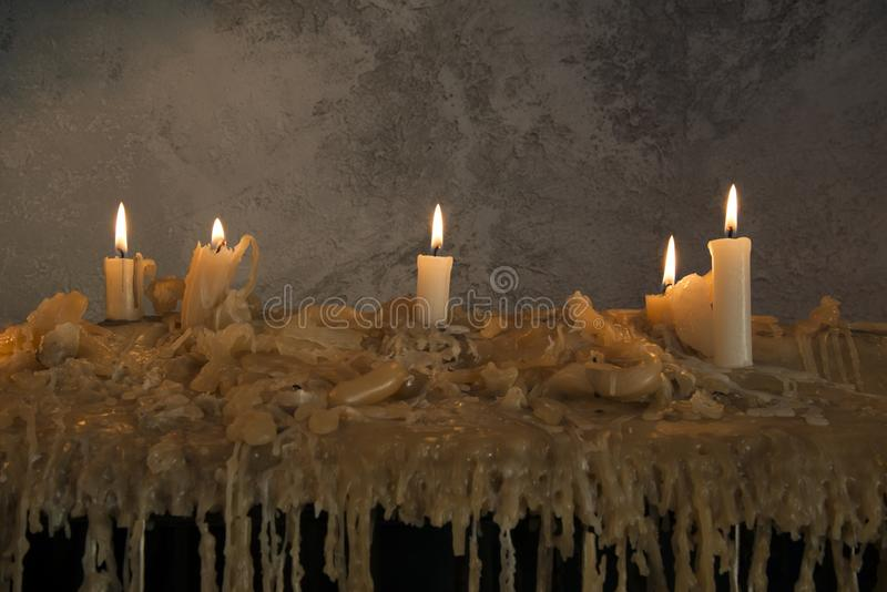 Burning candles on melted wax.many burning candles.Many burning candles. The flames caused by burning are beautiful lines royalty free stock photo