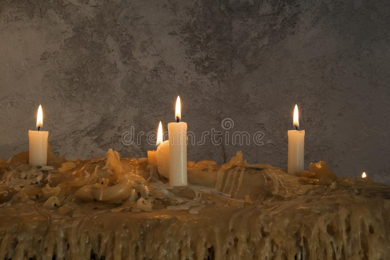 Burning candles on melted wax.many burning candles.Many burning candles. The flames caused by burning are beautiful lines royalty free stock photos