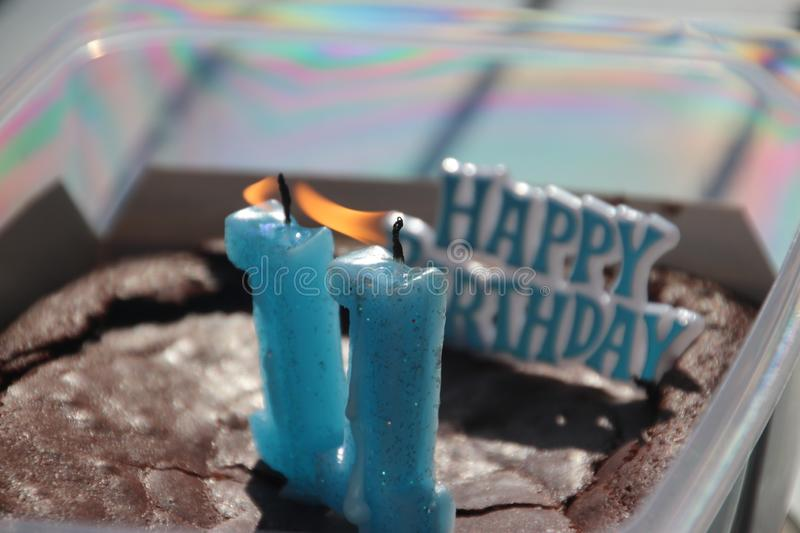 Burning candles number 1 makes 11 in a cake  for a birthday in blue color. royalty free stock images