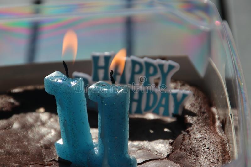 Burning candles number 1 makes 11 in a cake  for a birthday in blue color. royalty free stock photo