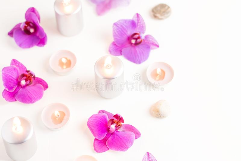 Burning candles and orchid flowers on wooden background. Relaxation spa concept royalty free stock photo