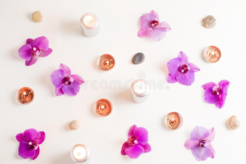 Burning candles and orchid flowers on wooden background. Relaxation spa concept stock photos