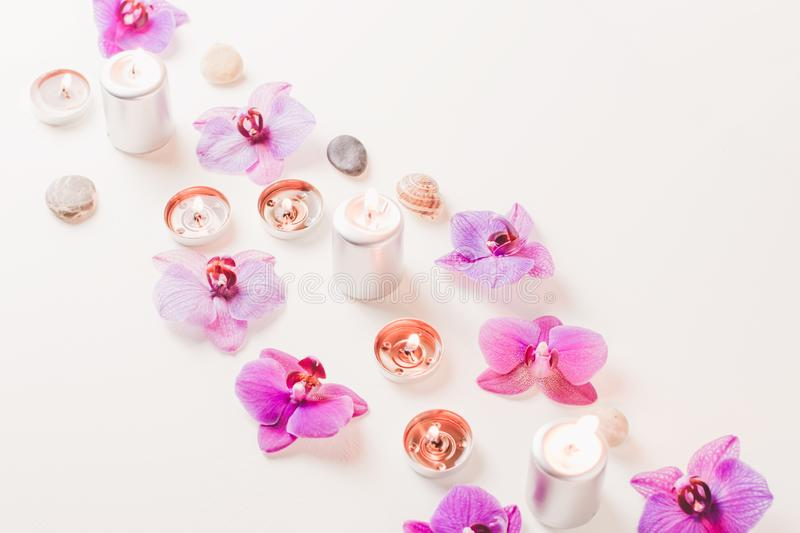 Burning candles and orchid flowers on wooden background. Relaxation spa concept stock images