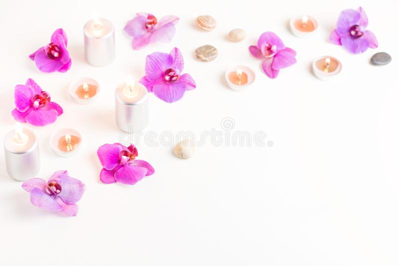 Burning candles and orchid flowers on wooden background. Relaxation spa concept stock photo