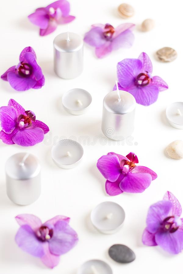 Burning candles and orchid flowers on wooden background. Relaxation spa concept stock image